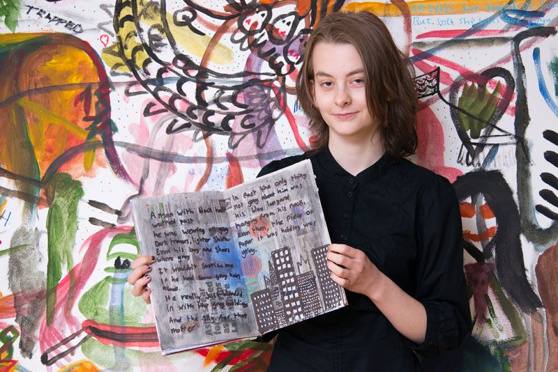Image of a student holding up some artwork with a mural in the background