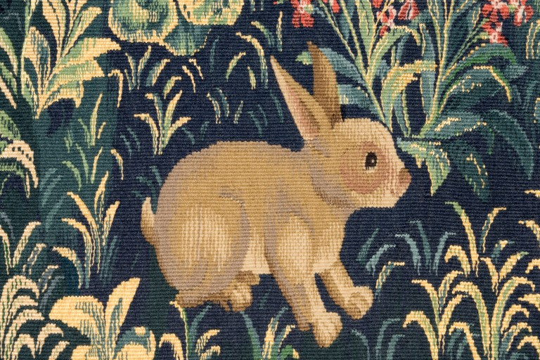 stitched rabbit surrounded by leaves and grass