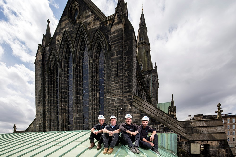 Four men sitting in a row on a green surface dressed in black and wearing hard hats with a cathedral behind them