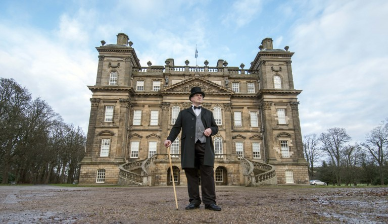 man in victorian dress stands leaning on a cane with a mansion in the background behind him