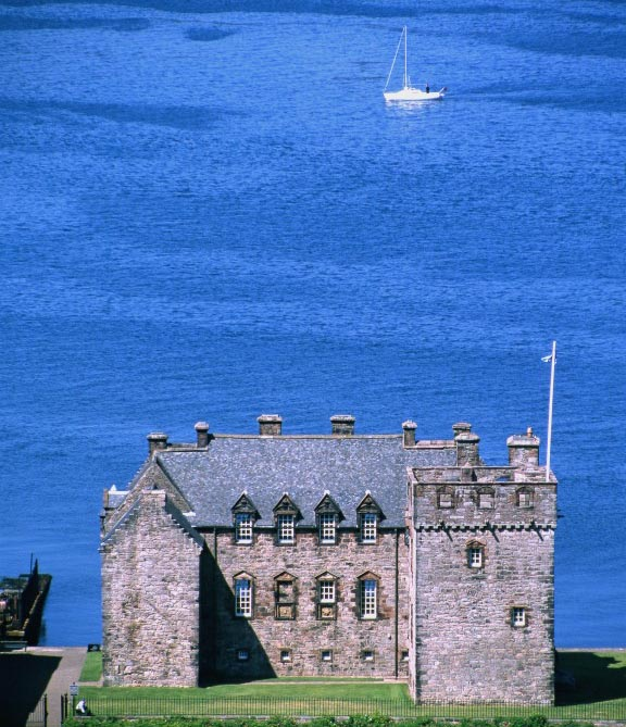 square castle building with blue sea behind and boat in the background