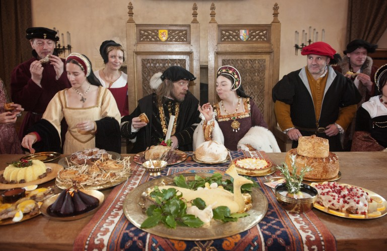 a table laid out with old fashioned types of food, with a row of people in renaissance costume behind including two royals seated on wooden thrones