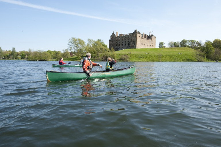canoe with two people sitting inside on a loch with a castle in the background