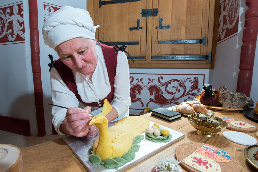 woman wearing white head scarf paints detail onto a pie made in the shape of a bird