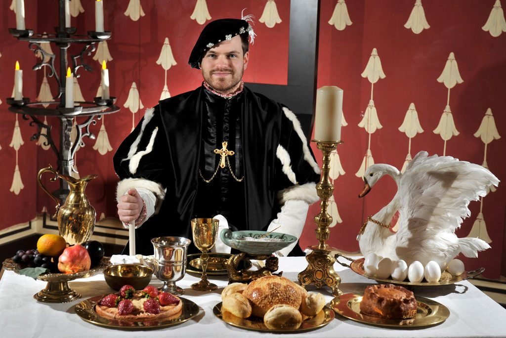 man in renaissance costume stands behind table of food including bread, pie, tart and swan