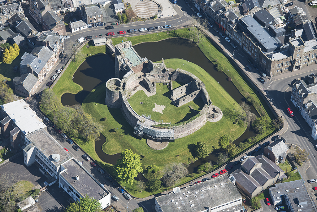 aerial view of a round castle wall with a moat around the outside in the centre of a town