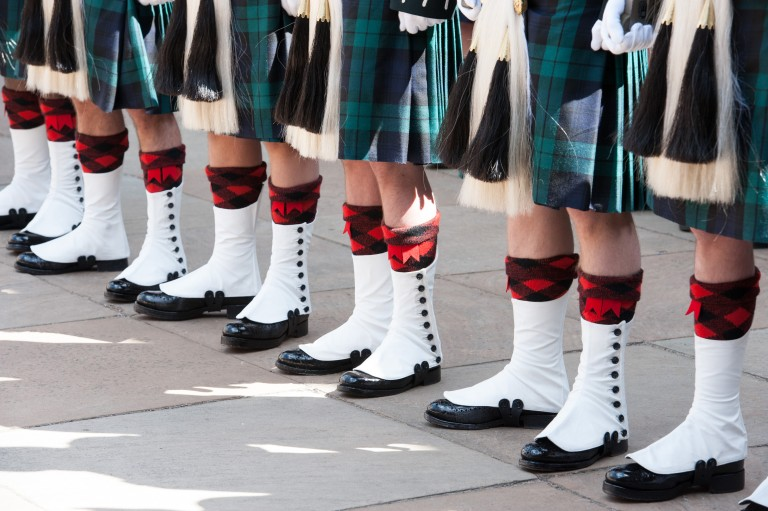 close up of 6 pairs of legs wearing army uniform socks, kilts and shoes