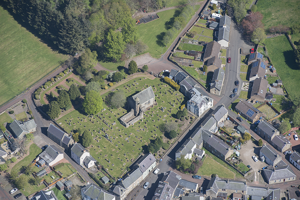 aerial image of a churchyard with a ruined chapel and many grave markers