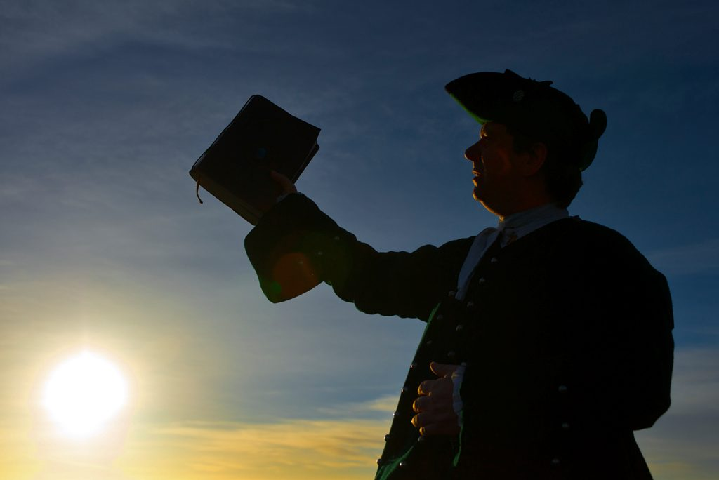 man in hat holds up book, silhoutted against a blue sky
