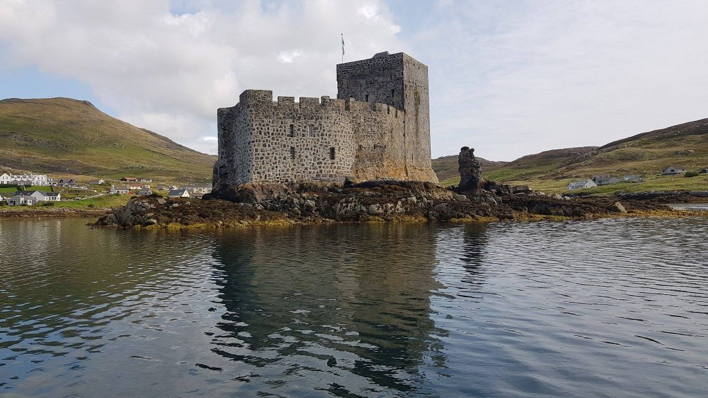 a grey stone castle with hills in the distance behind it and a body of water in front of it