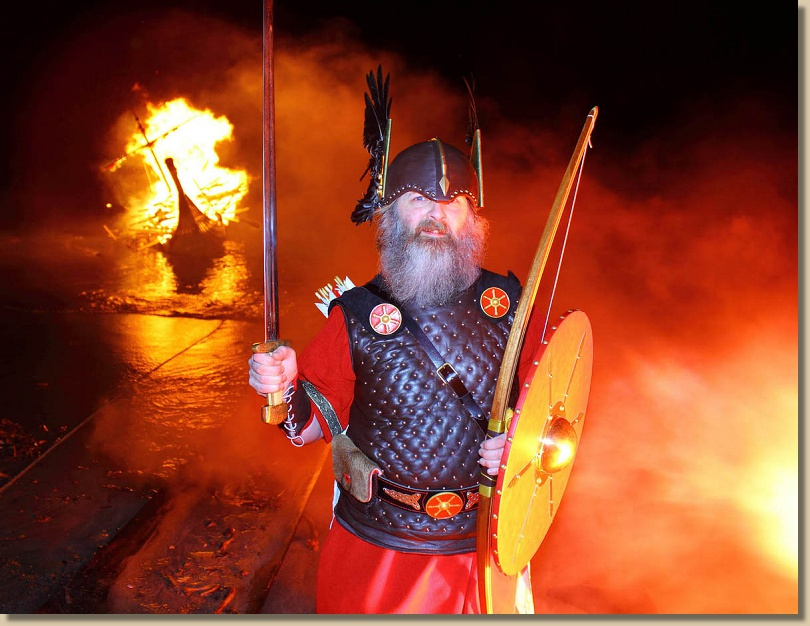 bearded man in helmet and armour stands before a burning boat