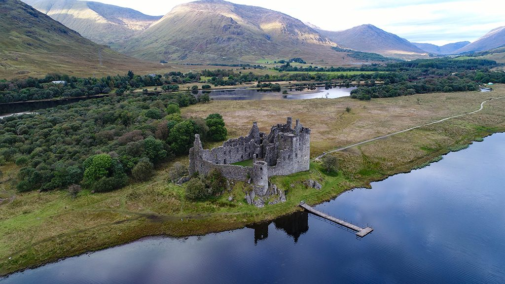 aerial image of ruined Kilchurn Castle with loch in front and mountains behind