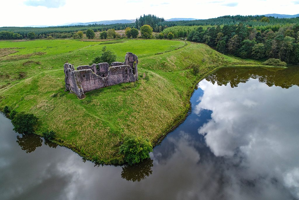 aerial view of a ruined castle on a green embankment with water in front