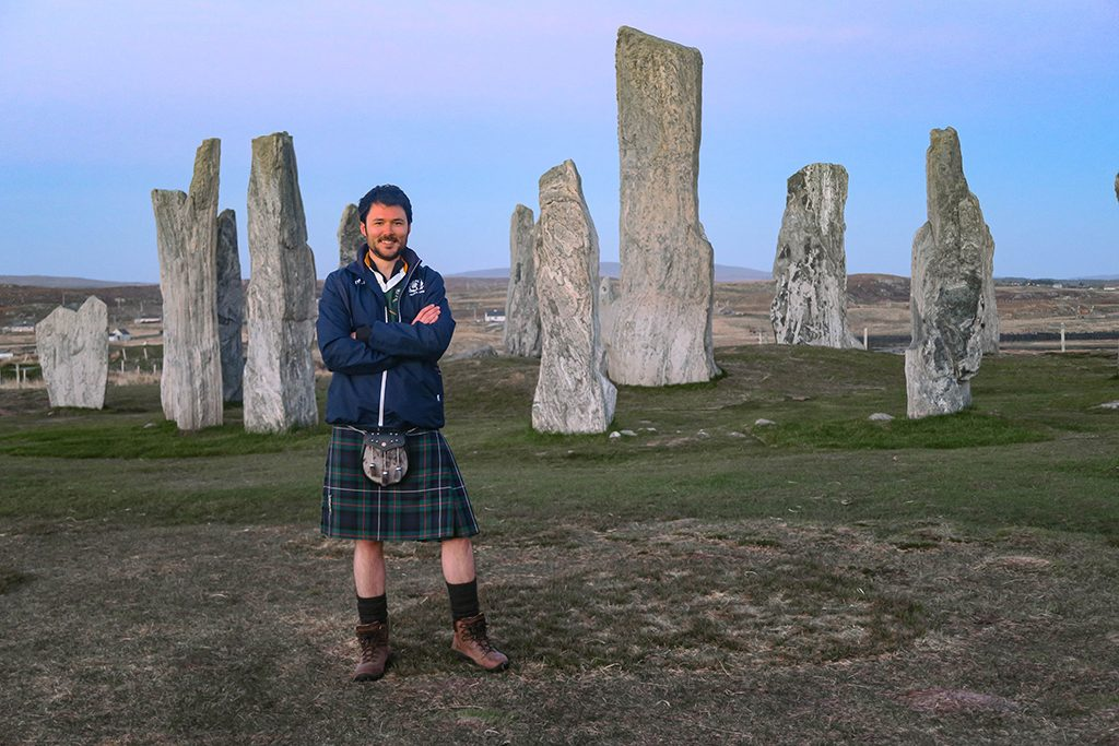 man in kilt smiles at camera with stone circle behind him