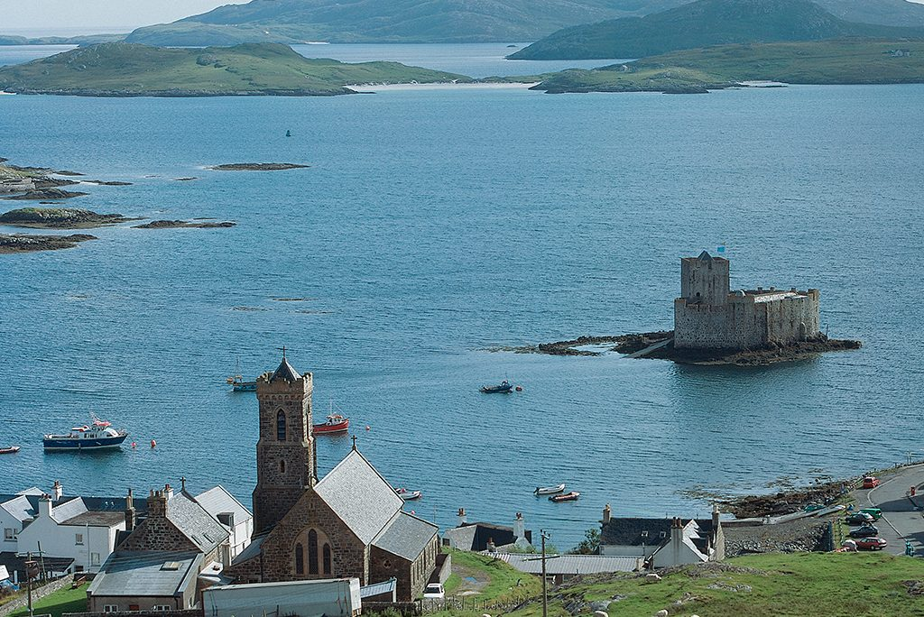 bay of blue water with buildings on coast in foreground, castle surrounded by water in the middle, and hills far in the distance