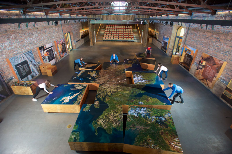 Image of a group of people assembling a large floor map of Scotland
