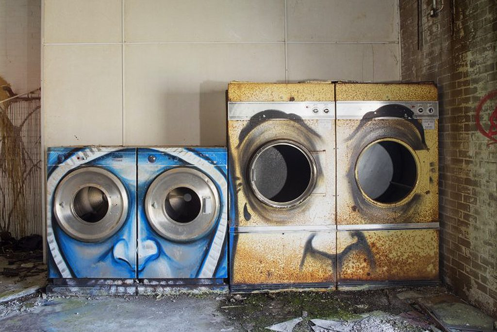 two graffiti faces painted on units in an abandoned building
