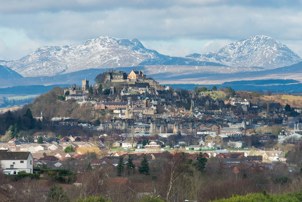 distant view of a city with a castle on a rock above rows of buildings and snowy mountains in the background