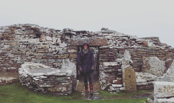 person bundled up in rain coat, boots and gloves smiles at the camera as she stands before an ancient stone building