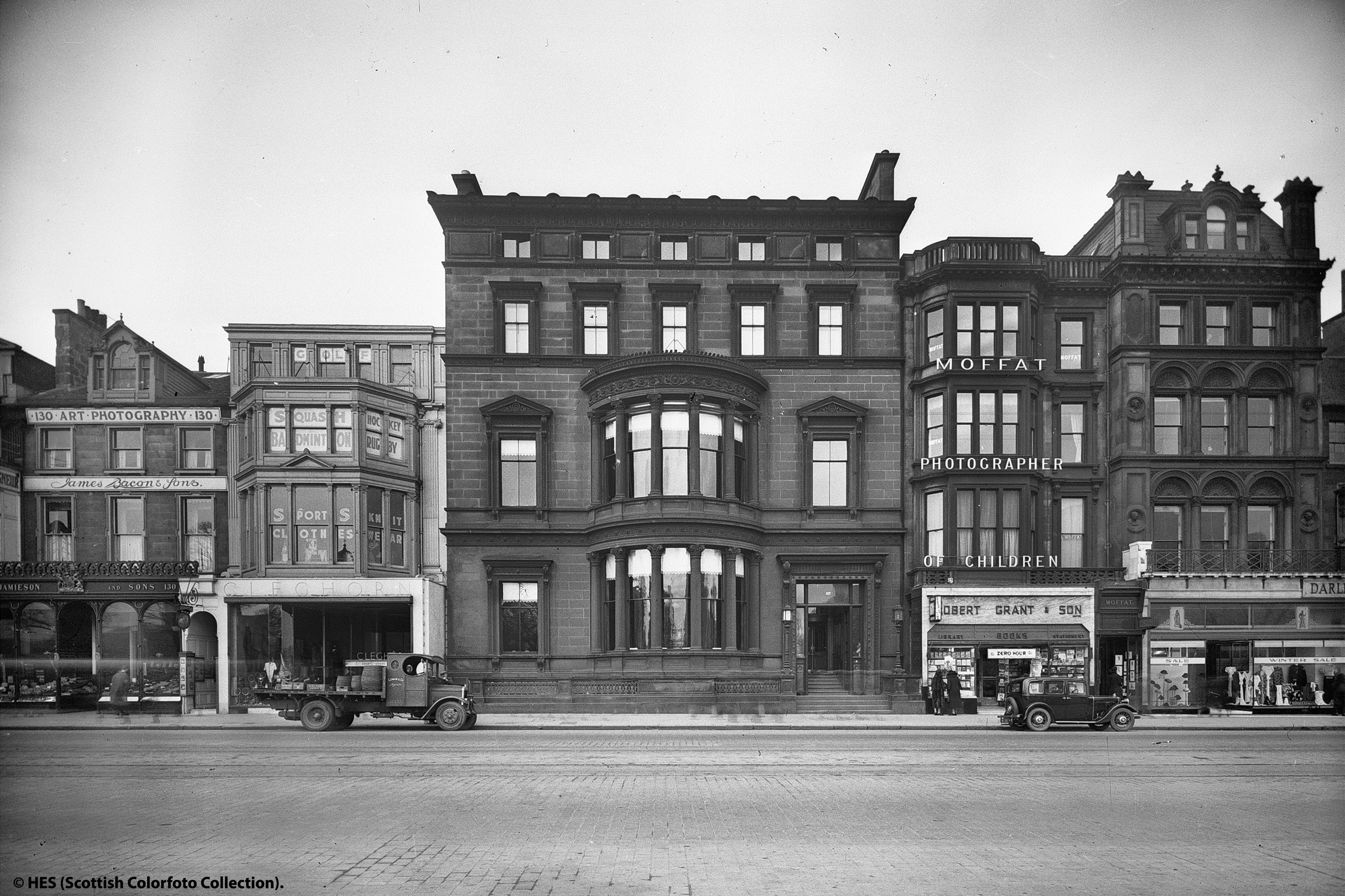 black and white image of four story high shop front with car parked in front