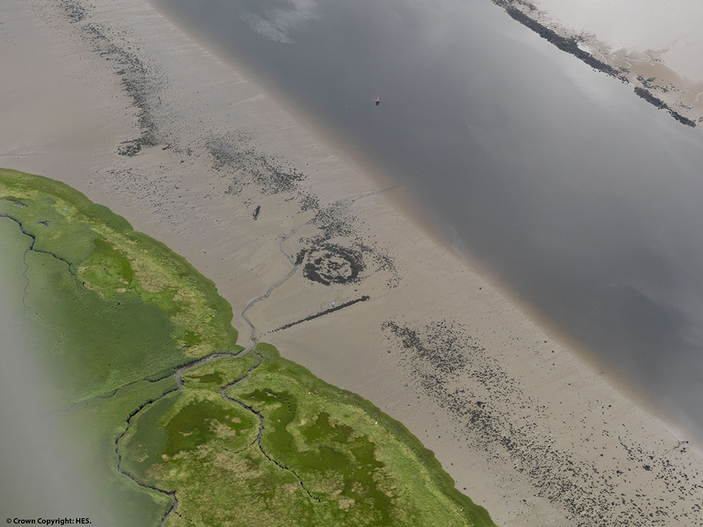 view from above of sandy beach with grey circle in the middle, lined at either side by green land and grey water