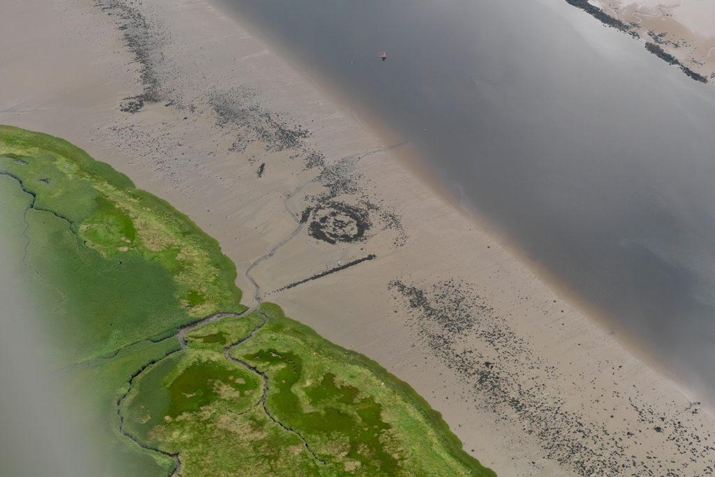 sandy beach with a circular archaeological feature in the centre