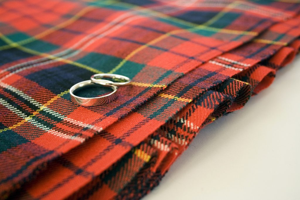 red and green tartan material lying on a white surface with two metal rings sitting on top