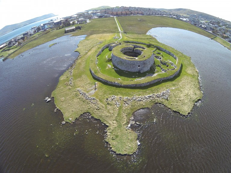 view looking down at a round stone building by the edge of some water