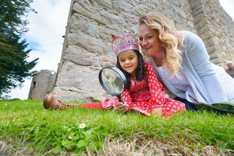 Mother and daughter sit at the foot of a castle and explore through a magnifying glass