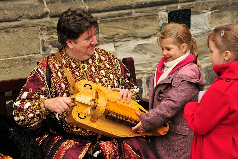Two children meet a man in historic costume and are shown a historic musical instrument