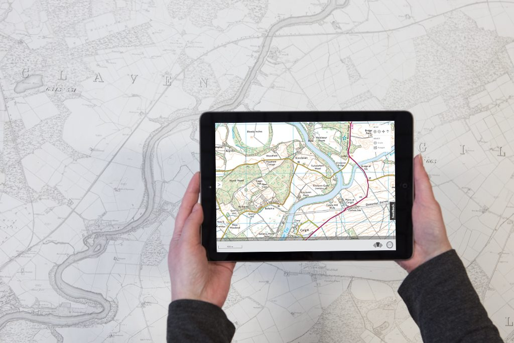 hands hold an electronic tablet showing a colourful map above a paper map showing a historic view