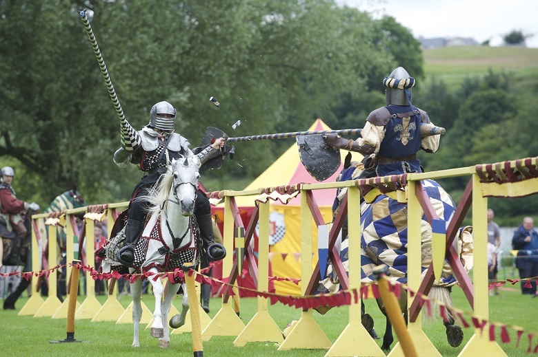 two reenactors dressed in medieval outfits charge at each other while jousting