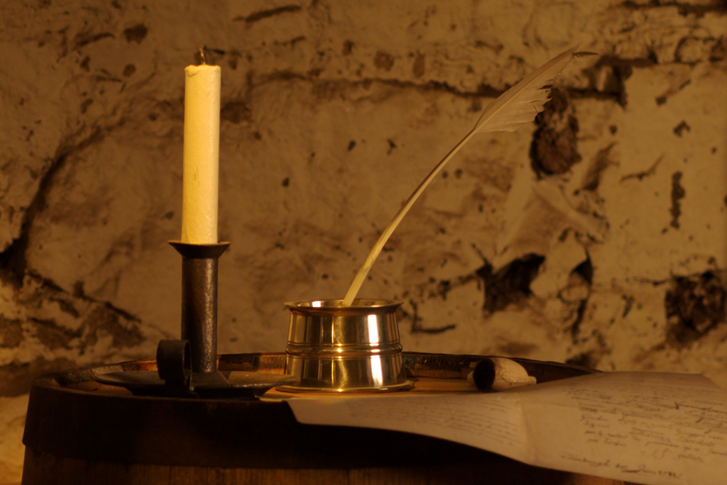 A candle, quill and manuscript sit on top of a barrel