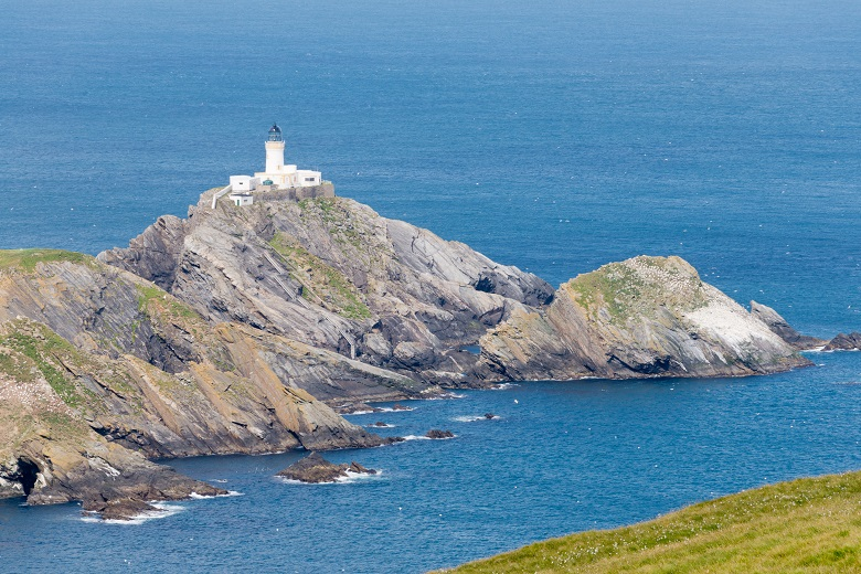 View of Muckle Flugga island. A white lighthouse sits atop a rocky outcrop in a calm blue sea
