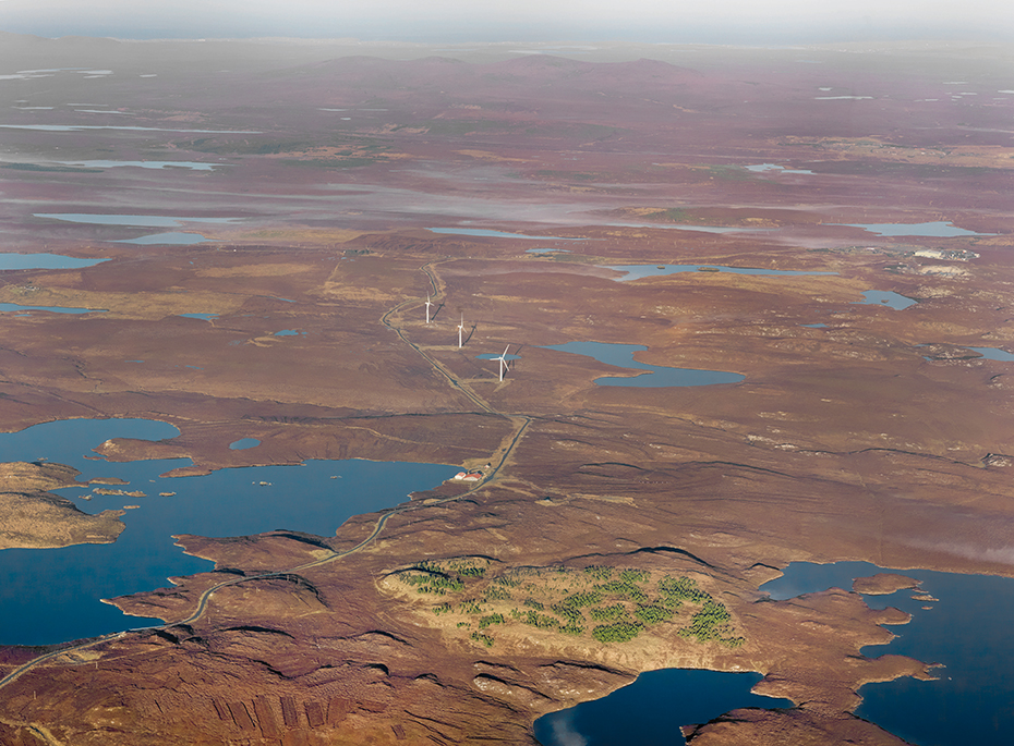 aerial image showing land bordered by water and wind turbines in the distance