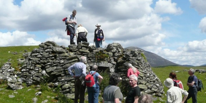 a group of people with backs to the camera congregate around remains of a stone building