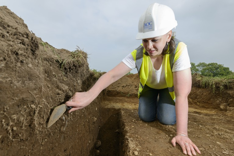 woman in hard had and high vis vest kneels in trench with trowel