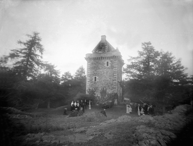 View of Fatlips Castle from 1898 with groups of people in Vitroian dress stood outside