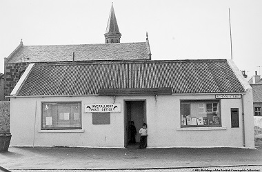 Black and white photo from the 1970s shows children lurking in the doorway of a post office
