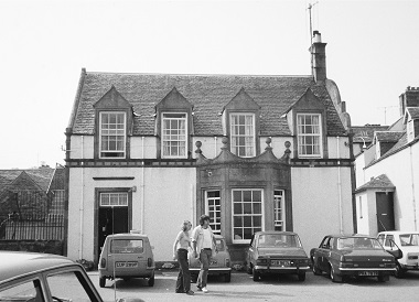 In the 1970s a couple walks in front of a pub holding hands