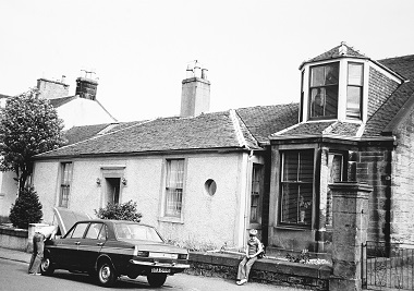 Black and white photo of a residential street in the 1970s. A boy sits on the garden wall while his dad fixes the car.