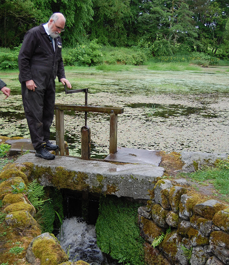 View of the mill pond at New Abbery Corn Mill with a man opening the sluice gates to let water through