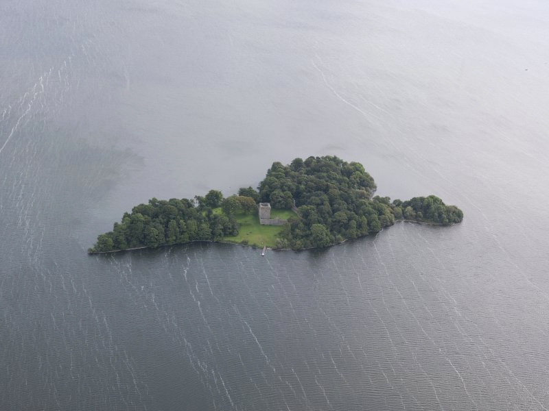 aerial view of an island covered in trees with a castle in the middle