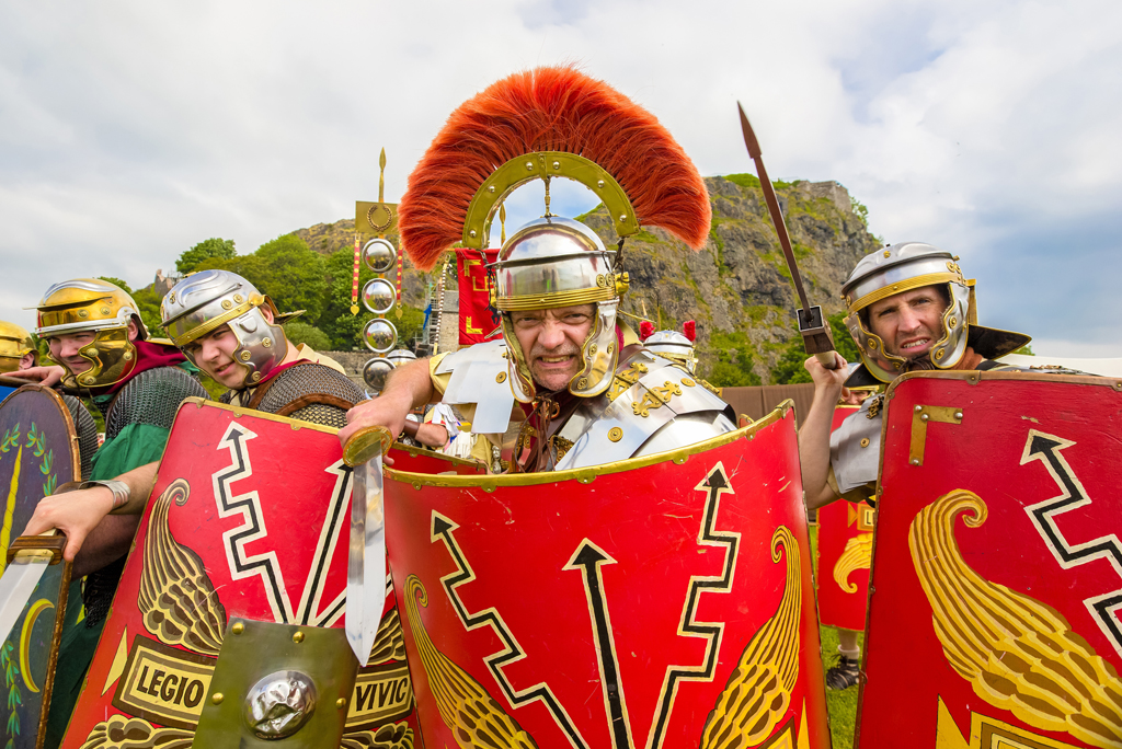 four men in roman helmets charge towards camera holding weapons and shields