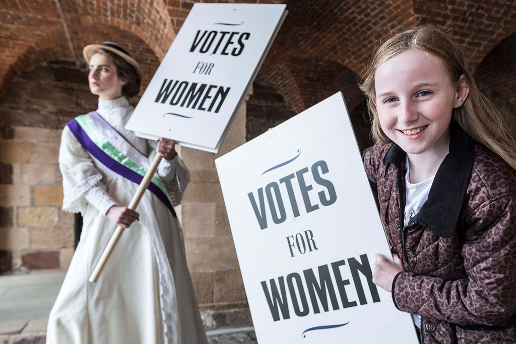 woman in victorian dress and young girl in modern dress hold signs saying 'votes for women'