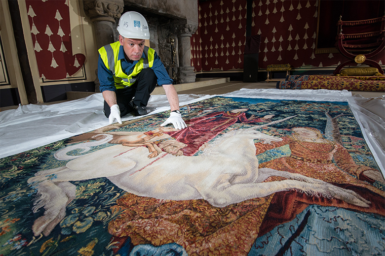 Man bends over a Unicorn tapestry on the hall floor