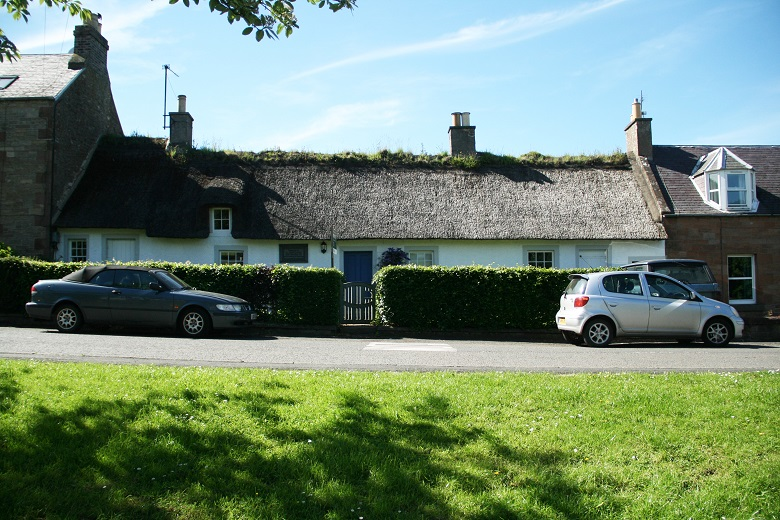 A thatched cottage surrounded by a hedge