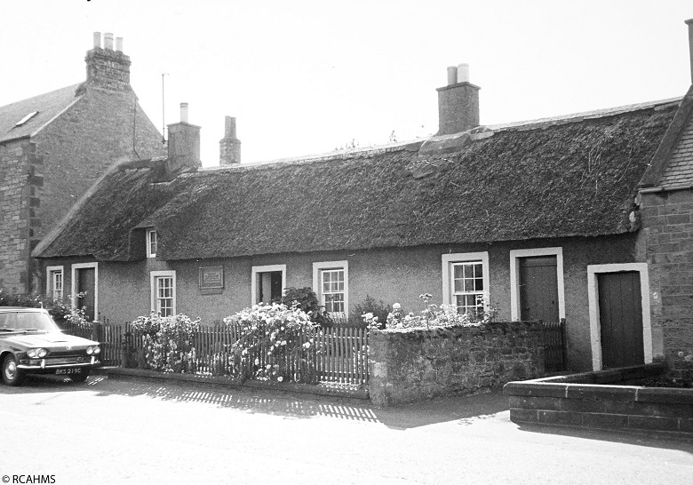 A black and white photo of a traditional Scottish thatched cottage