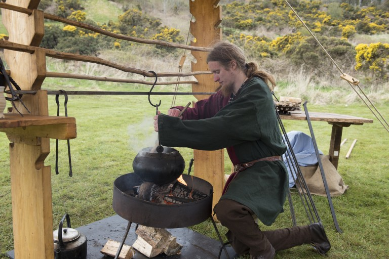 man in medieval dress stirs a cauldron