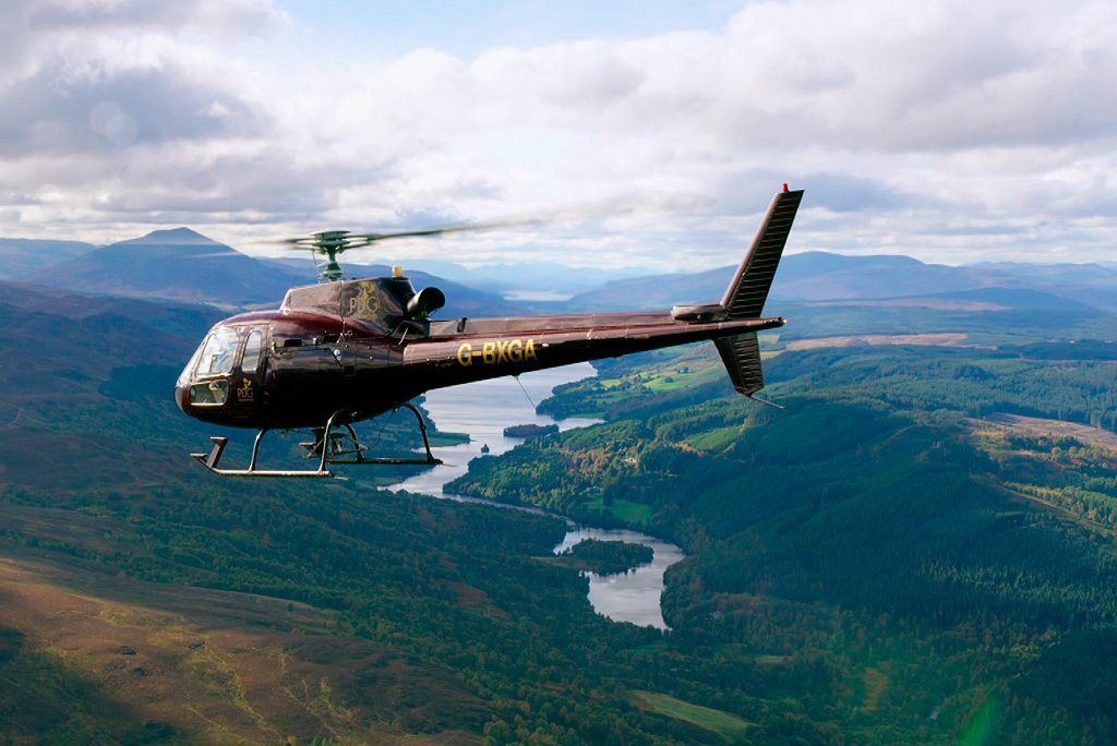 helicopter flying over landscape with forest and river